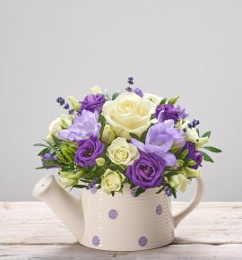 'Purple Rain' - large headed ivory rose planted in a spotted ceramic watering can pot with purple freesia, purple lisianthus, white spray roses and dried lavender. Perfect gift idea.
