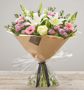 Hand-tied 'Pure Pastels' fresh flower arrangement. Includes, white LA lilies, Ivory Large Headed Roses, pink spray chrysanthemums, white antirrhinums and pink germini/