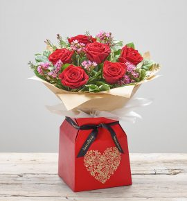 Bernard Chapman red roses arrangement in red and gold heart gift box - 'Ruby Kisses' red large headed roses with thlaspi, wax flower, pittosporum and salal.