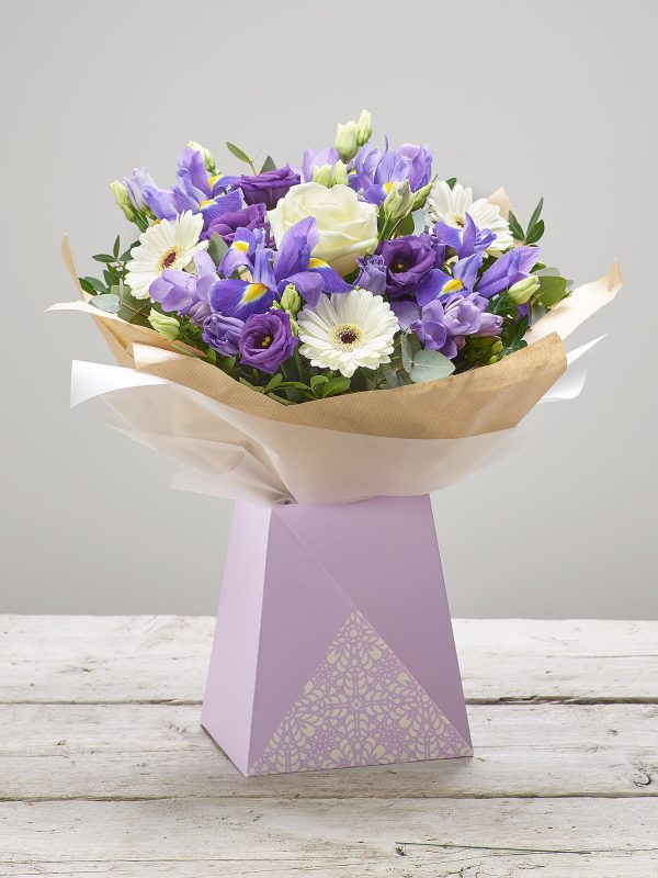 Bernard Chapman 'Amethyst Dusk' flower bouquet presented in a pretty lilac gift box - Featuring ivory large headed roses, purple freesia, white germini, purple lisianthus and blue iris with pistache and eucalyptus. (Code: C14220BS)