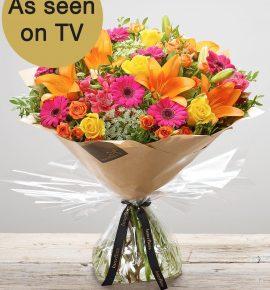 Large 'Flaming Fiesta' hand-tied fresh flower arrangement. Yellow large headed roses, orange spray roses, orange lilies, cerise alstroemeria, white ammi and cerise germini. (Code: C15012VS)