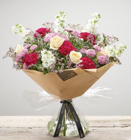 Large 'Pomegranate Punch' Hand-tied flower arrangement. Featuring cream large headed roses, cerise carnations, white stocks, pink spray chrysanthemums and pink limonium. Available at online at bernardchapman.co.uk and in store in Harlow and Braintree. 'Code: S33522MS'