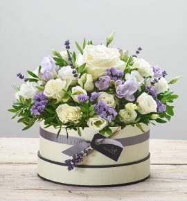 'Lovely Lilacs' flower arrangement - Ivory large headed rose, purple freesia, white spray roses, white lisianthus and lilac statice with pistache and dried lavender, presented in a soft cream and black hatbox. (Code: C14271BS)