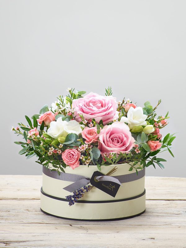 'Rose Blush' fresh flower arrangement presented in a soft cream and black hatbox - Featuring pink large headed roses, white freesia, pink spray roses, and pink waxflower with eucalyptus. (Code: C14251PS)