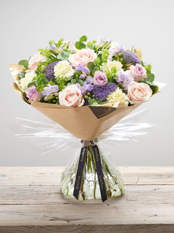 'Dusky Mauve' hand created floral bouquet featuring cream carnations, pale pink large headed roses, lilac large headed roses, lilac freesia, lilac trachelium and bupleurum. (Code: L20921MS)