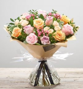'Darling Rose' hand-tied, fresh flower arrangement available for next day delivery. Featuring pink, peach and lilac large headed roses, cerise bouvardia and cream spray roses, hand-tied with pistache and pittosporum. (Code: L21151MS)