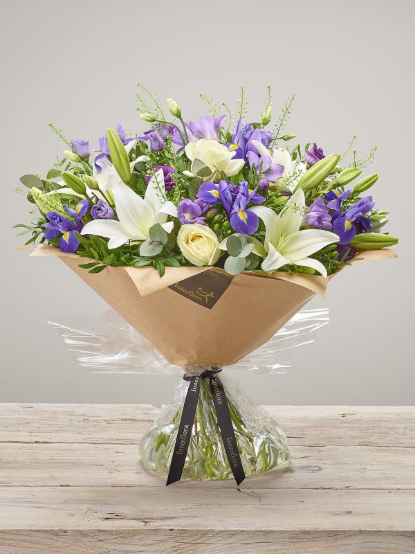 'Violet Vibes' exquisite large hand-tied flower bouquet. Featuring ivory large headed roses, purple freesia, blue iris, white LA lilies and purple lisianthus hand-tied with thlaspi, pistache and eucalyptus. (Code: C14350BS)