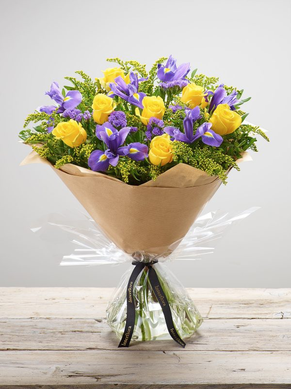 Large 'Golden Skies' hand-tied floral arrangement with large headed yellow roses, blue iris, purple statice and yellow solidago available from Bernard Chapman in Braintree and Harlow. (Code: S33512MS)