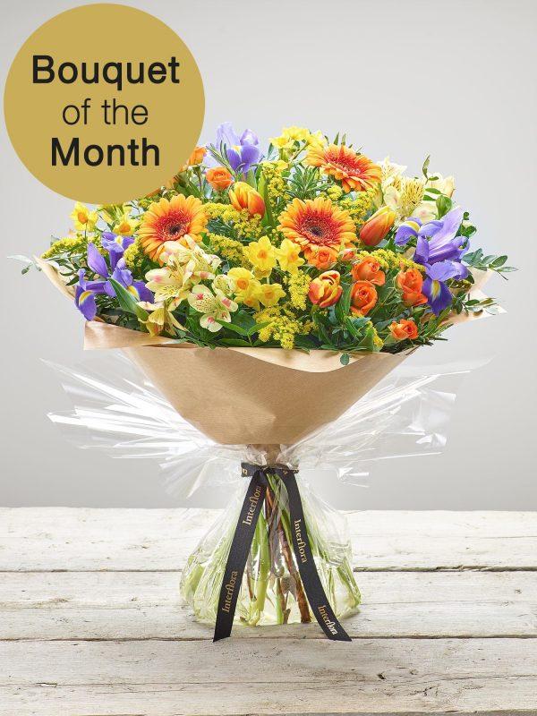 'Sunny Days' hand-tied flowers - Yellow narcissi, lemon alstroemeria, orange germini, blue iris, orange spray roses, red/yellow tulips and yellow solidago with pistache and rosemary. (Code: S33450MS)