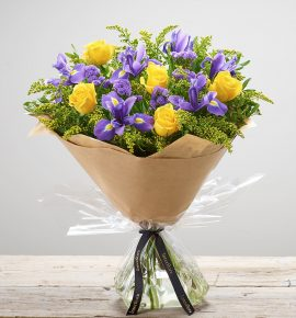 'Golden Skies' - Yellow and purple hand-tied flower bouquet, featuring yellow large headed roses, blue iris, purple statice and yellow solidago available from Bernard Chapman florists. (Code: S33510MS)