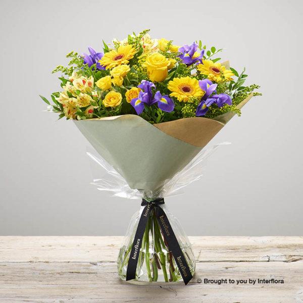 'Sunshine Memories' hand-tied yellow flower bouquet - Featuring yellow large headed roses, yellow spray roses, lemon alstroemeria, yellow germini, blue iris and yellow solidago. (Code: M53500MO)