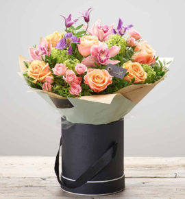 Plush Orchid bouquet presented in a tall black and cream hatbox - Peach large headed roses, purple clematis, salmon large headed roses, green viburnum opulus, pink cymbidium orchids and pink spray roses with pistache. Available at online at bernardchapman.co.uk and in store in Harlow and Braintree. Perfect gift for Mother's Day. (Code: M53541MS)