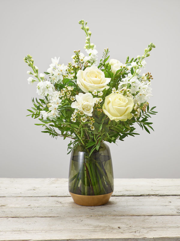 Fragrant Whites Vase - Large headed roses, white freesia, white narcissi, white stocks and white waxflower arranged in a green glass vase available in store and online and at bernardchapman.co.uk (Code: S33580WS)