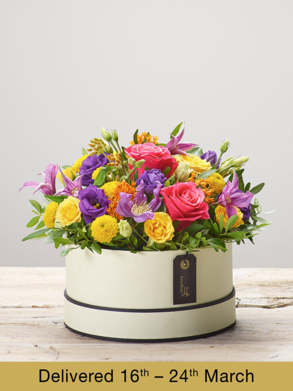 'Beaming Brights' flower arrangement presented in a soft cream and black hatbox Hatbox - Perfect Gift Idea. Featuring cerise large headed roses, orange asclepia, a yellow spray rose, a purple lisianthus, a yellow spray chrysanthemum, a purple clematis and pistache. (Code: M53481MS)
