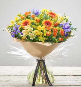 'Sunny Days' bright hand-tied flowers - Featuring yellow narcissi, lemon alstroemeria, orange germini, blue iris, orange spray roses, red/yellow tulips and yellow solidago with pistache and rosemary. (Code: S33450MS)