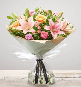 'Strawberry Ice: Hand-tied flower bouquet available from Bernard Chapman - Featuring pink, lilac and peach large headed roses with pink LA lilies, pink spray roses and pistache. (Code: M53530MS)