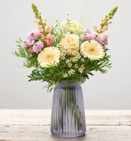 Bernard Chapman Sweet Vanilla Vase - Pink antirrhinums, a cream large headed rose, pink spray chrysanthemums, cream germini and white tanacetum with pistache and panicum grass, arranged in a lilac vase. (Code: M53511MS)